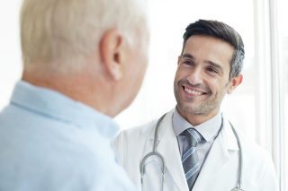 1-male-doctor-smiling-at-patient-science-photo-library